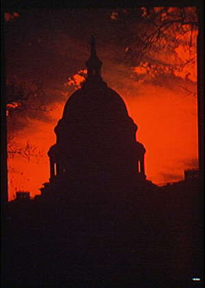 U.S. Capitol exteriors. U.S. Capitol silhouetted against orange sky, with clouds