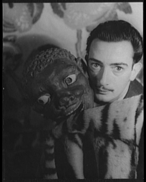 [Portrait of Salvador Dali with carved black head adjacent to his face]