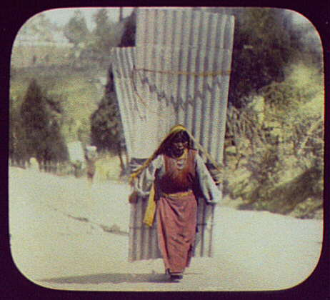 Woman carrying large corrugated sheets