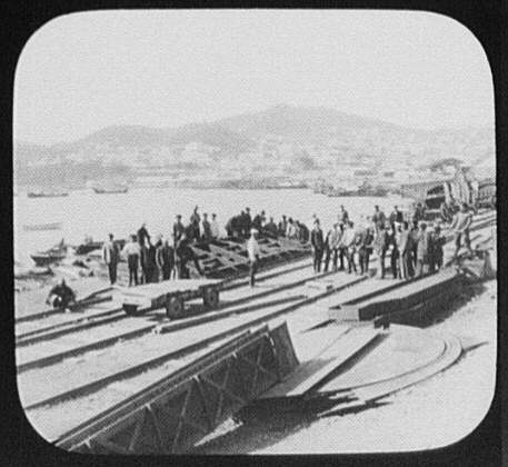 Vladivostok - laborers at dockside railroad tracks; city and harbor in background