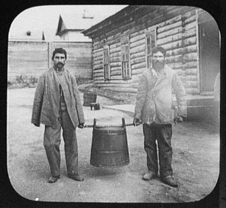 Two convicts carrying large pot of soup
