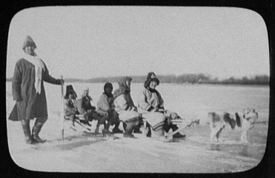 Man standing beside 5 Goldi women and children on dog sledge